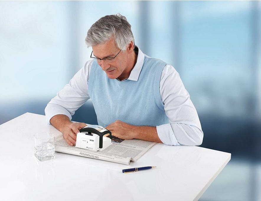 Mann sitzt am Tisch und liest mit einem Lesegerät die Zeitung