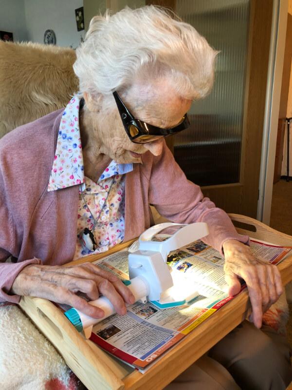 Seniorin liest mit Lupe die Zeitung
