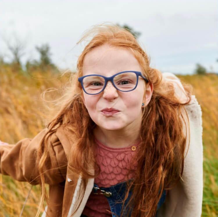 Lustiges Mädchen mit roten Haaren trägt Brille