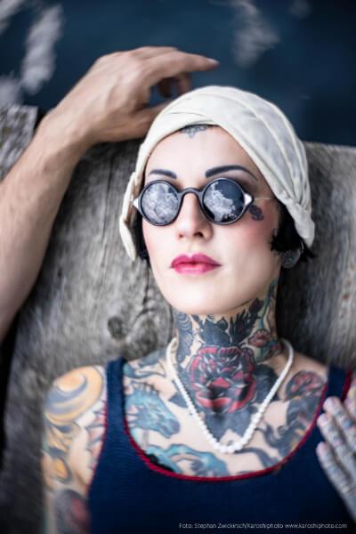 Tätowierte Frau in Badeanzug mit Sonnenbrille