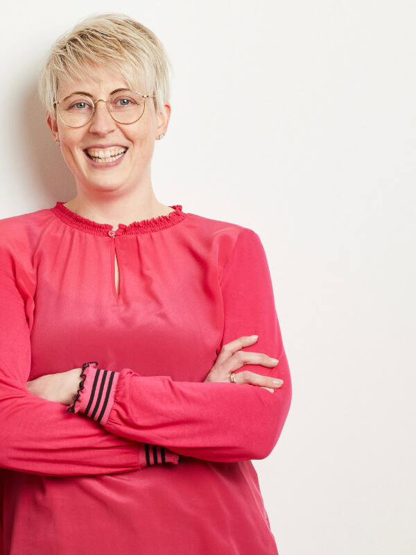 Tanja Natalizi mit Brille und rotem Top