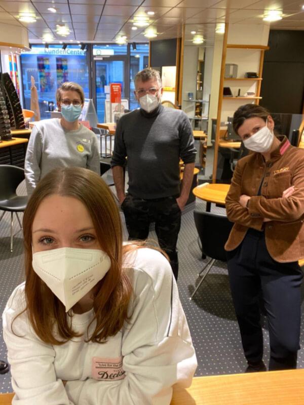 Team und Kundin mit Maske